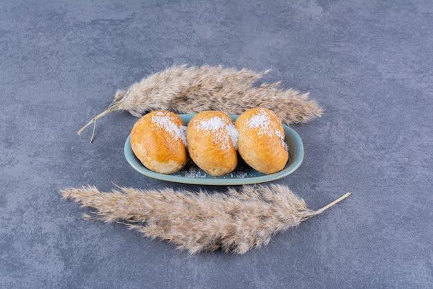 Une assiette bleue de gâteaux sucrés avec du sucre et des épis de blé sur pierre.