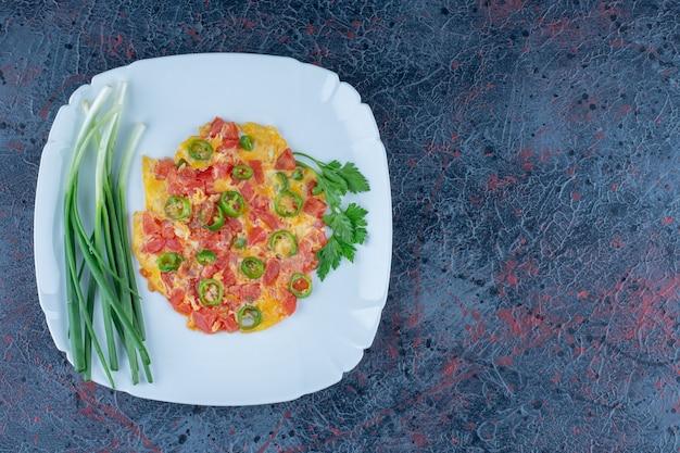 Une assiette bleue d'œufs au plat avec des légumes