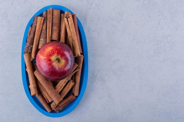 Assiette bleue pleine de bâtons de cannelle et pomme sur pierre.