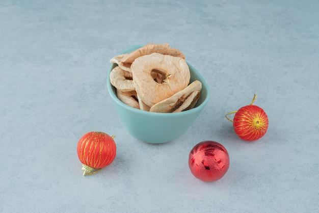 Une assiette bleue pleine de fruits secs et sains avec des boules rouges de noël. photo de haute qualité