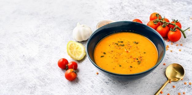 Assiette bleue avec soupe de lentilles rouges et légumes