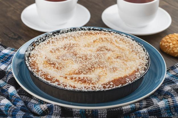 Assiette bleue de tarte sucrée avec des pépites de noix de coco, tasse de thé et biscuits sur une surface en bois