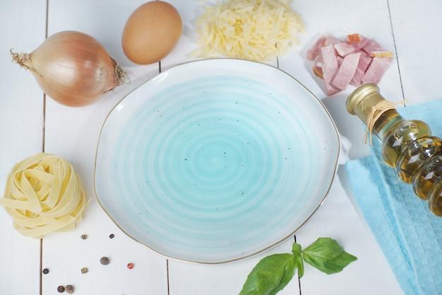 Assiette bleue vide sur une table en bois blanc avec des ingrédients répartis sur le bord pour faire de la pâte de carbonara.