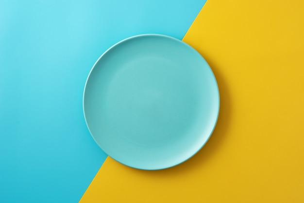 Assiette bleue vide sur table jaune et bleue