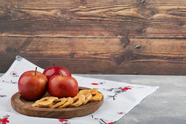 Assiette en bois d'anneaux de pomme séchée et pomme rouge sur nappe blanche.