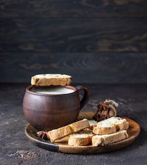Assiette en bois avec biscuits italiens traditionnels et une tasse de café.