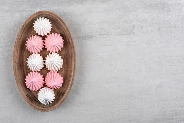 Assiette en bois de bonbons meringués blancs et roses sur table en pierre.
