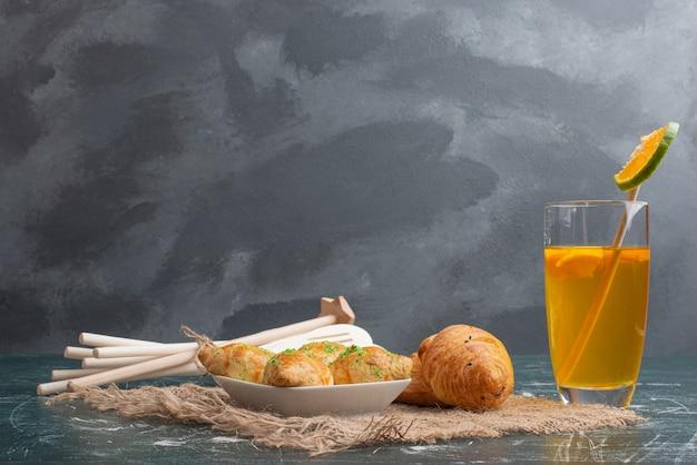 Assiette en bois de boulangerie avec ustensiles de cuisine sur marbre.