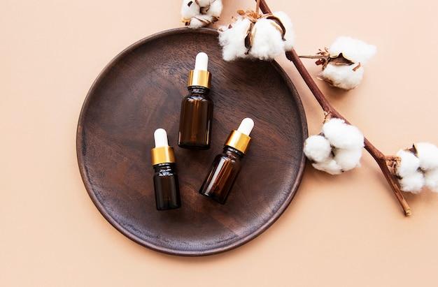 Assiette en bois avec des bouteilles d'huile essentielle