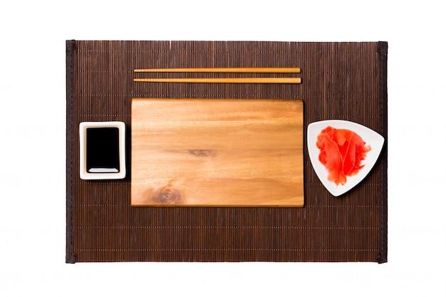 Assiette en bois brun rectangulaire vide avec des baguettes pour sushi, gingembre et sauce soja sur fond mat en bambou foncé. vue de dessus avec espace de copie pour votre conception