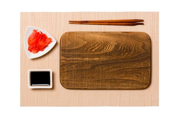 Assiette en bois brun rectangulaire vide avec des baguettes pour sushi, gingembre et sauce soja sur fond de tapis de sushi brun. vue de dessus avec espace de copie pour votre conception
