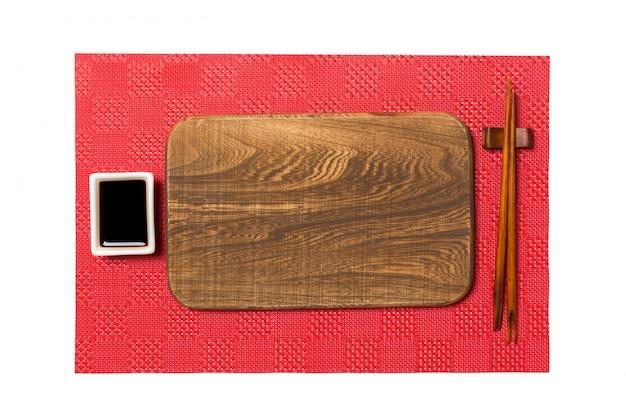 Assiette en bois brun rectangulaire vide avec des baguettes pour sushi et sauce soja sur fond de sushi mat rouge