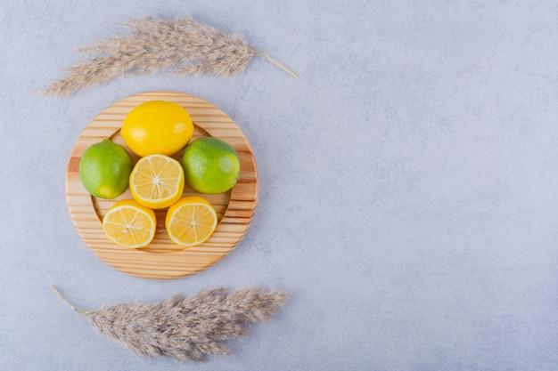 Assiette en bois de citrons frais juteux sur pierre.