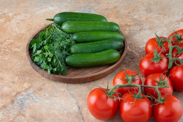 Une assiette en bois avec des concombres, des légumes verts et des tomates.