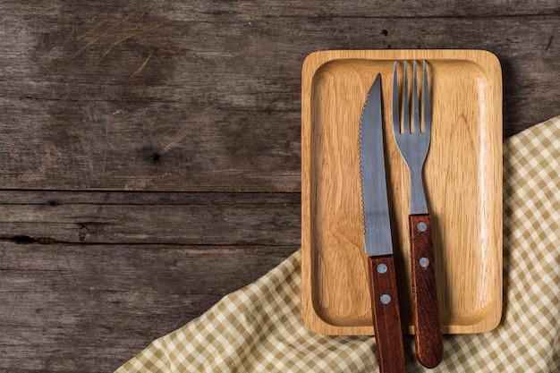 Assiette en bois avec couteau à steak sur fond en bois