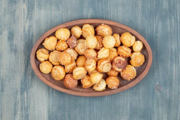 Assiette en bois de craquelins ronds aux graines de sésame sur une surface en bois.