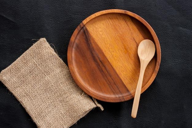 Assiette en bois et cuillère en bois mise sur un sac de cuisine fait maison