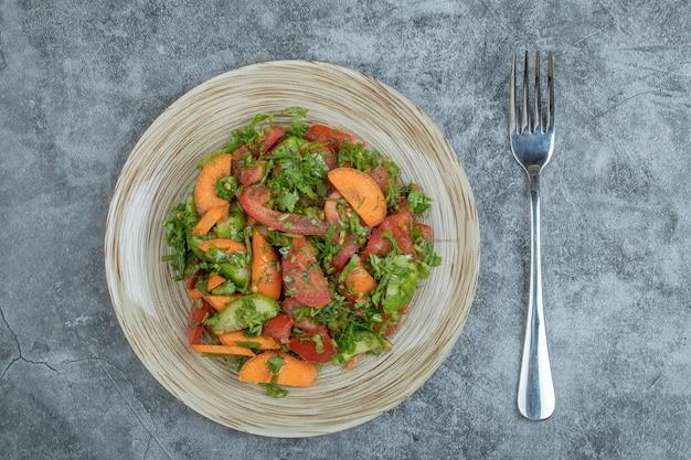 Une assiette en bois de délicieuse salade de légumes.