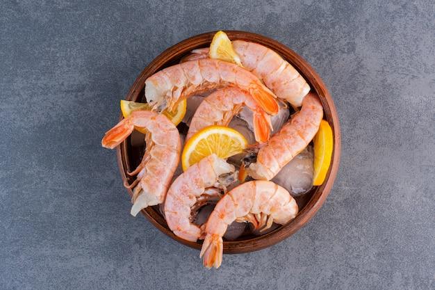 Une assiette en bois de délicieuses crevettes avec des glaçons et des tranches de citron sur une surface en pierre