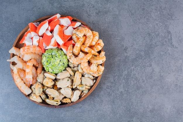 Une assiette en bois de délicieuses crevettes avec de savoureux bâtonnets de crabe sur une surface en pierre