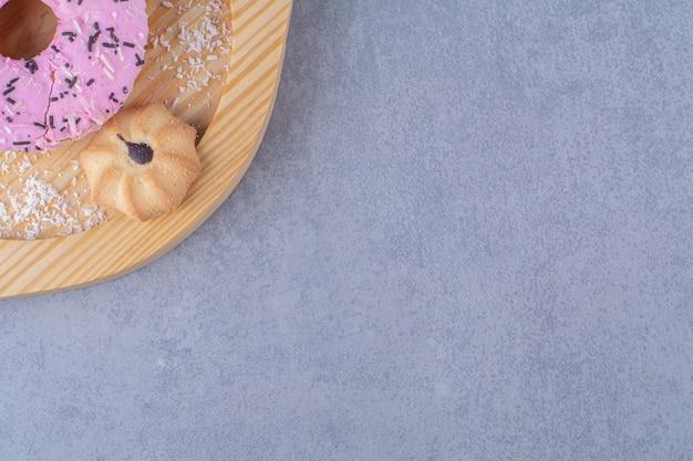 Une assiette en bois de délicieux beignet rose avec biscuit sucré.
