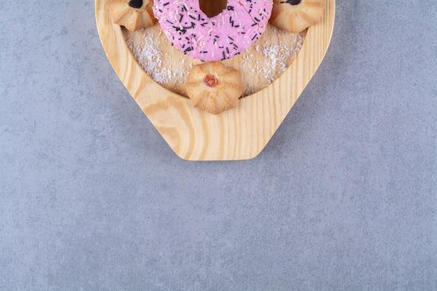 Une assiette en bois de délicieux beignet rose avec un biscuit sucré.