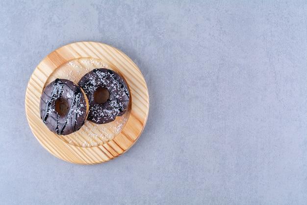 Une assiette en bois de délicieux beignets au chocolat avec des pépites.