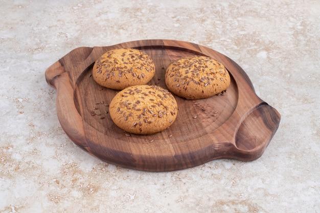 Une assiette en bois de délicieux biscuits avec des graines sur une table en pierre.