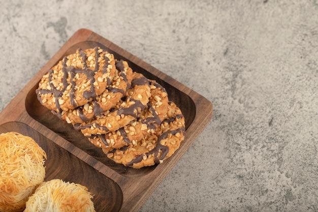 Assiette en bois de desserts sucrés mixtes placés sur la pierre.