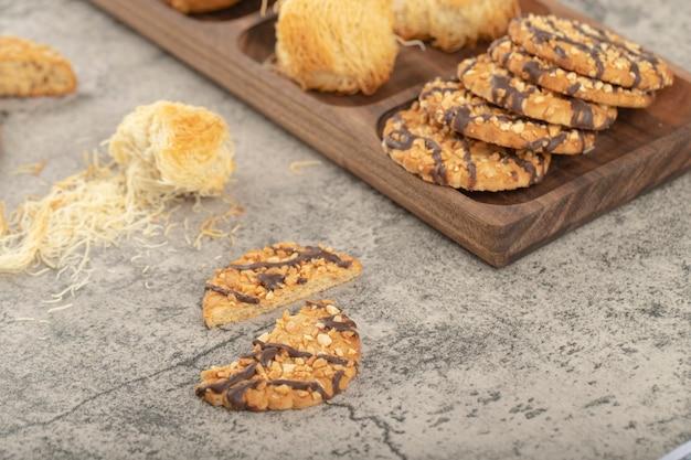 Assiette en bois de divers desserts sucrés placés sur la pierre.
