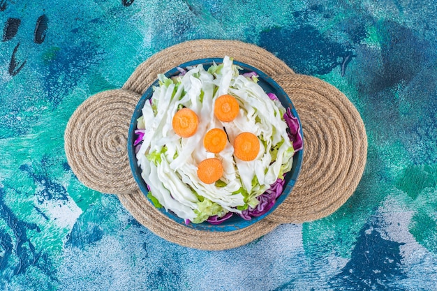 Une assiette en bois de divers légumes sur un dessous de plat