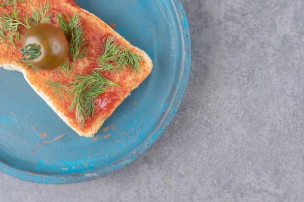 Une assiette en bois avec du pain grillé sur une surface en marbre