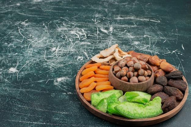 Assiette en bois avec fruits secs sur table en marbre
