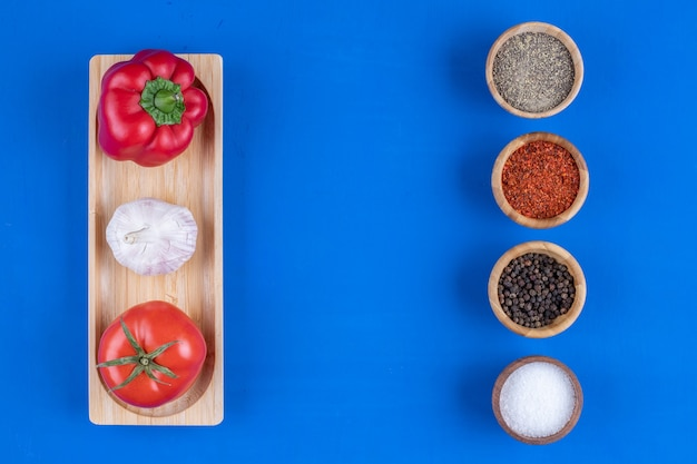 Assiette en bois de légumes frais mûrs avec diverses épices.