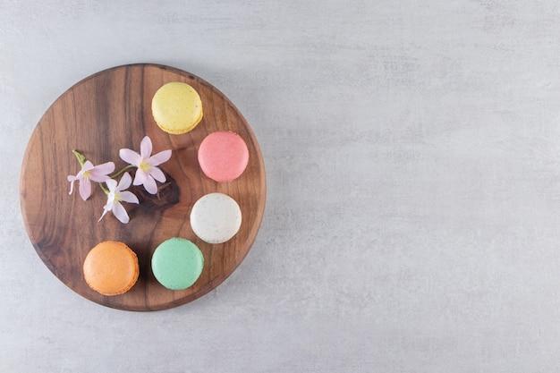 Assiette en bois de macarons sucrés colorés avec des fleurs sur fond de pierre.