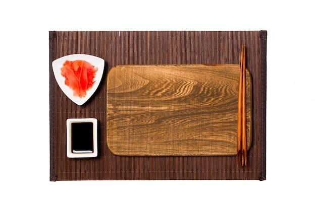 Assiette en bois marron rectangulaire vide avec baguettes pour sushi, gingembre et sauce soja sur tapis de bambou foncé. vue de dessus avec fond