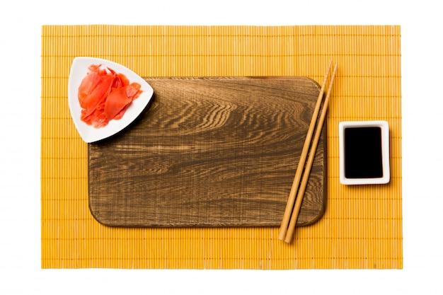 Assiette en bois marron rectangulaire vide avec des baguettes pour sushi et sauce soja sur jaune