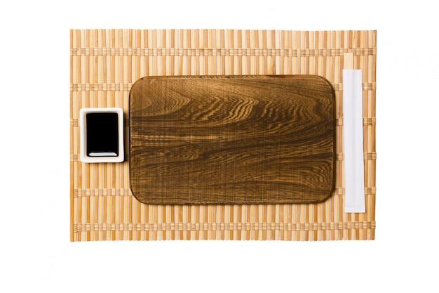 Assiette en bois marron rectangulaire vide avec baguettes pour sushi et sauce soja sur tapis en bambou jaune