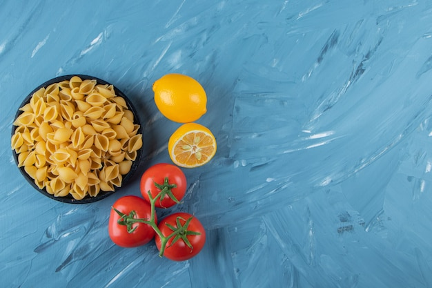 Une assiette en bois noir de pâtes crues au citron et aux tomates rouges fraîches.
