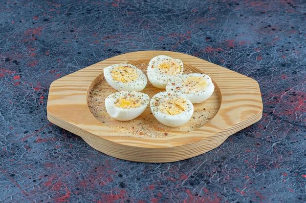 Une assiette en bois avec des œufs durs aux épices.