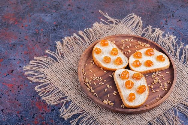 Assiette en bois de pain blanc avec confiture de baies sur toile de jute.