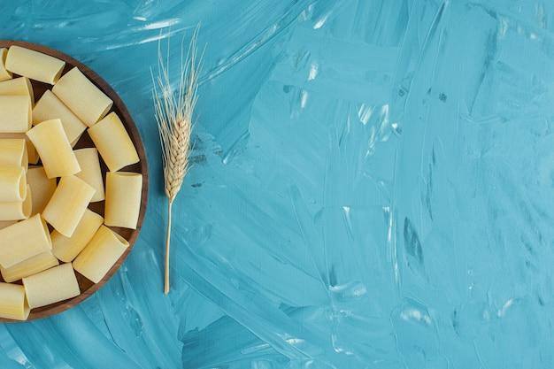 Assiette en bois de pâtes rigatoni sèches crues sur fond bleu.