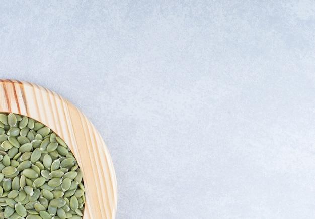 Assiette en bois avec un petit talon de graines de citrouille vertes non décortiquées sur une surface en marbre