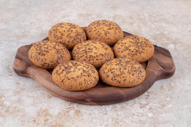 Assiette en bois pleine de biscuits à l'avoine sur une surface en marbre.