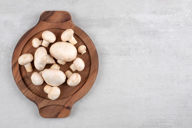 Une assiette en bois pleine de champignons frais placés sur un fond de pierre.