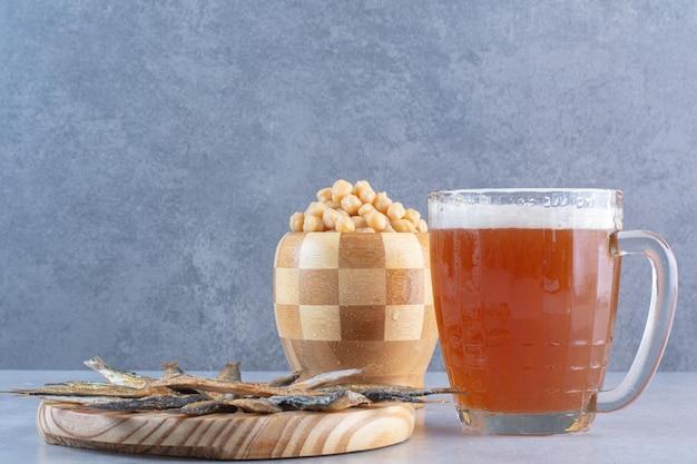 Une assiette en bois pleine de délicieux poissons avec de la bière et des petits pois