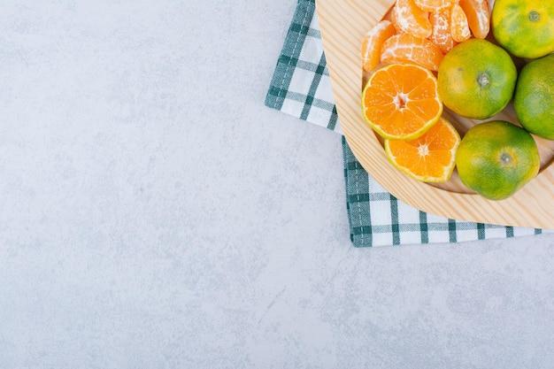 Assiette en bois pleine de mandarines aigres sur blanc