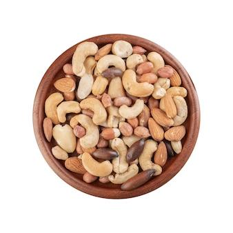 Assiette en bois pleine de noix mélangées,. arachides, noix du brésil, noix de cajou, baru et amandes.