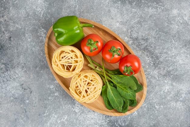 Assiette en bois pleine de nouilles et de légumes crus sur une surface en marbre.