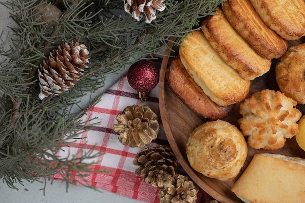 Une assiette en bois pleine de pâtisseries sucrées avec des boules de noël et des pommes de pin